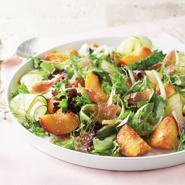 Ribbons of zucchini with prosciutto, sliced peaches, and mixed greens