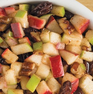Multicolored chopped apples with skin, dried fruit, nuts and sprinkle of cinnamon in a white bowl