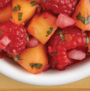 Chopped fresh mango with whole fresh strawberries, and chopped herbs in a small white bowl