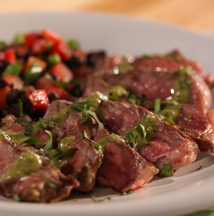 Sliced rib eye steak topped with green chili-lime dressing with side of chopped tomatoes, peppers, and black beans