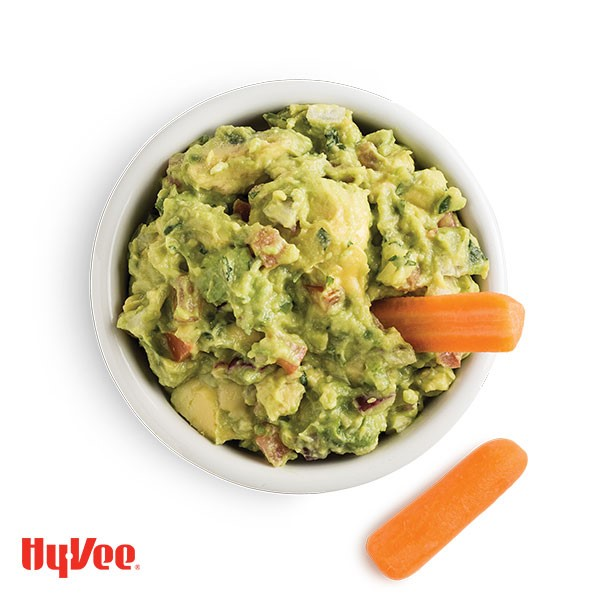 Bowl of chunky guacamole with carrot sticks