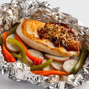 Aluminum foil filled with BBQ cheddar chicken, radishes and red and green bell peppers