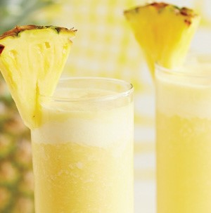 Yellow pineapple smoothies in tall glasses with pineapple wedge on rim