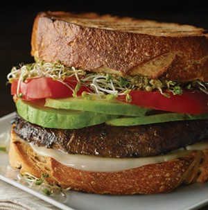 Grilled bread topped with melted cheese, portobella mushroom, sliced avocados, sliced tomatoes, and bean sprouts