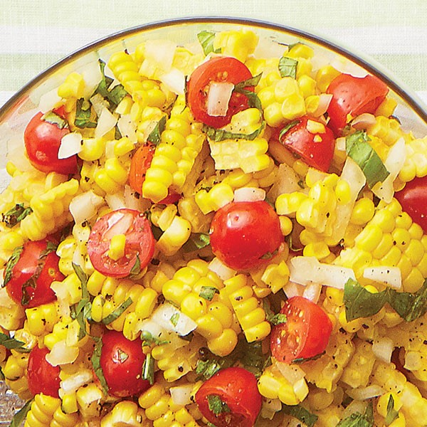 Clear bowl filled with fresh corn, halved cherry tomatoes, sliced basil, and chopped white onion