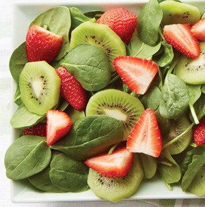 Spinach mixed with sliced stawberries and sliced kiwi