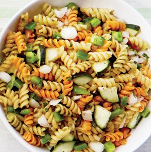 Red, green, and white spiral pasta mixed with green peppers and onions