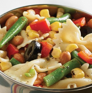 Bowl filled with bow tie pasta, green beans, corn kernels, diced red peppers, and sliced black olives