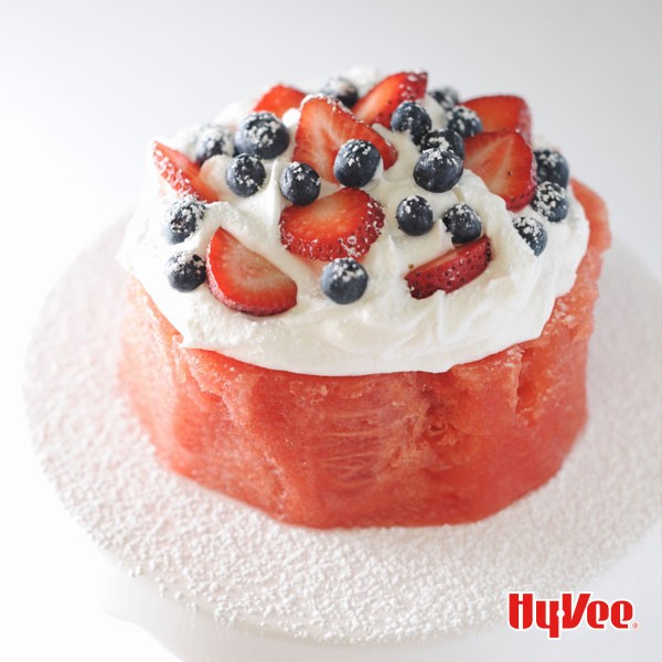 Thick circular piece of watermelon with whipped topping, halved strawberries, whole blueberries, and sprinkled with powdered sugar