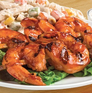 BBQ shrimp over plate of pasta salad