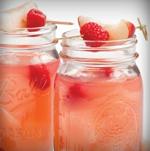 Mason jars filled with pink raspberry nectarine lemonade and topped with skewers of whole raspberries and nectarine wedge