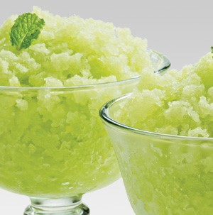 Glass ice cream dishes filled with green melon granita slush and garnished with a fresh mint leaf