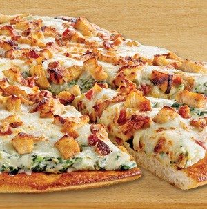 Pizza topped with white alfredo sauce, wilted spinach, and chopped cooked chicken on a wooden cutting board