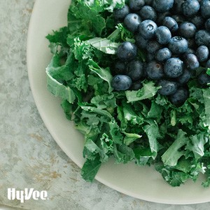 Chopped kale topped with fresh whole blueberries on a white circular plate