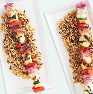 Platter of chicken and vegetable kabobs over rice