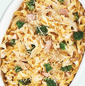 Noodles topped with tuna, broccoli florets, and melted cheese in casserole dish