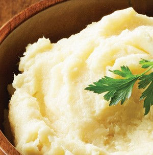 Mashed parsnips in a wooden bowl garnished with fresh Italian parsley