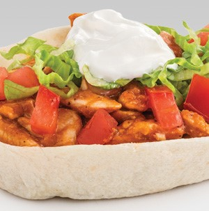 Flour taco bowls packed with chicken, chopped tomatoes, shredded lettuce, and dollop of sour cream