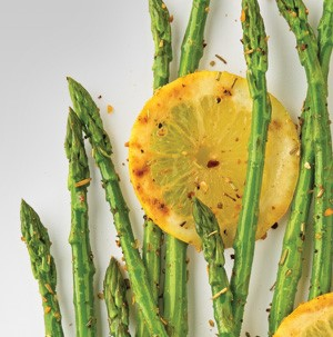Cooked asparagus seasoned and garnished with lemon