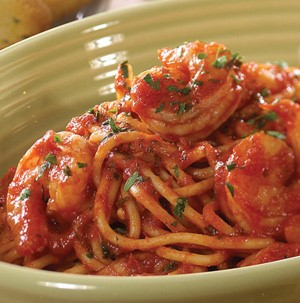Spaghetti topped with red sauce, cooked shrimp, and finely chopped parsley in a green bowl
