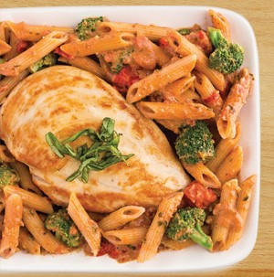 Baked chicken on top of tomato and pesto penne pasta, broccoli florets, and fresh basil