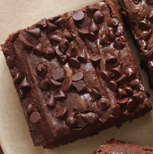 Black bean brownie squares on parchment paper topped with mini chocolate chips