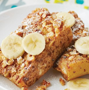 Plate of brie-stuffed banana french toast garnished with banana slices, pecans and sprinkles of powdered sugar