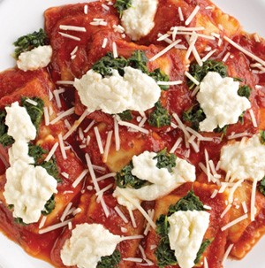 Ravioli topped with red sauce, wilted spinach, ricotta cheese, and shredded Parmesan