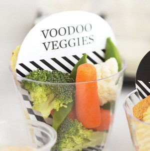 Clear veggie cups with baby carrots, broccoli, and cauliflower with a white sign on top