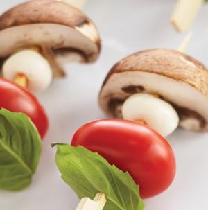 Basil leaf, cherry tomato, mozzarella ball and mushroom on wooden skewers