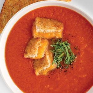 Tomato-basil soup with cheesy croutons, sliced basil, and freshly ground black pepper