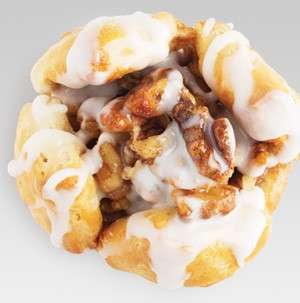 Biscuit cinnamon roll topped with chopped nuts and homemade glaze