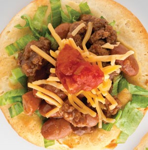 Biscuit topped with ground beef, beans, shredded lettuce, shredded cheese, and dollop of red salsa