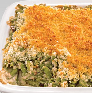 White casserole dish filled with creamy green beans and a crumbled bread crumb topping