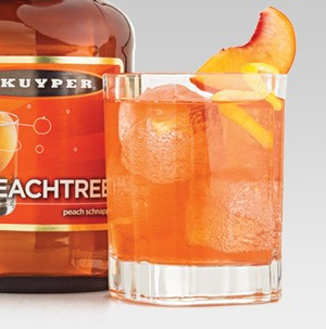 Glass filled with orange Royal Peach drink and topped with a peach slice and lemon peel
