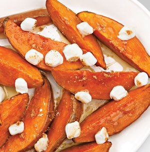 Thick sweet potato wedges topped with toasted mini marshmallows and drizzled with melted butter and brown sugar
