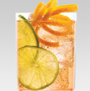 Glass filled with ice, rum punch, lime slices, and orange peel