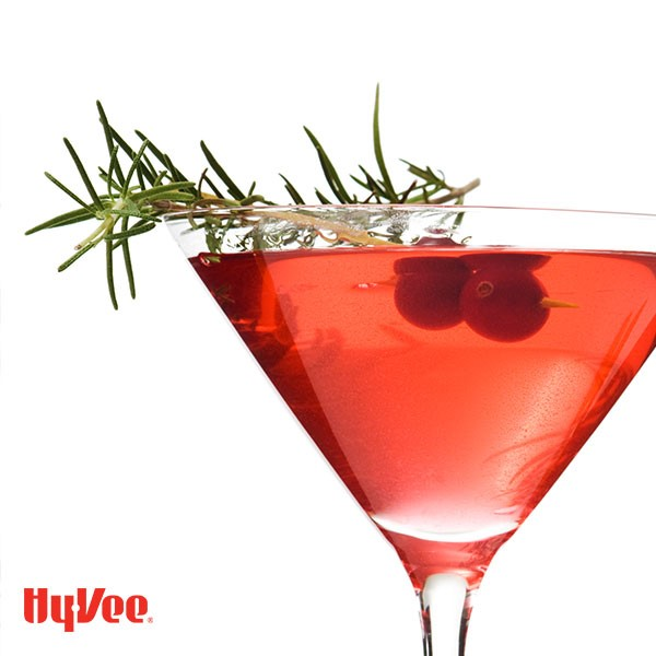 Glass of Christmas martini, garnished with rosemary and pomegranate seeds