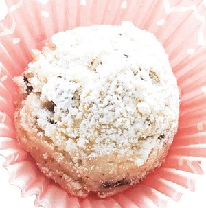 Snowball cookies in a pink cupcake liner dusted with powdered sugar
