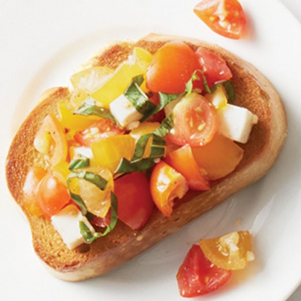 Toasted bread topped with mozzarella cubes, halved yellow and red cherry tomatoes, and fresh chopped basil