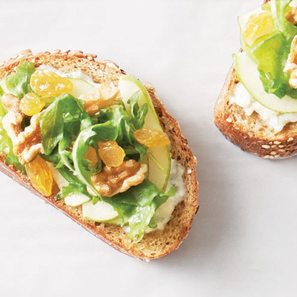 Toasted bread topped with arugula, walnuts, and golden raisins