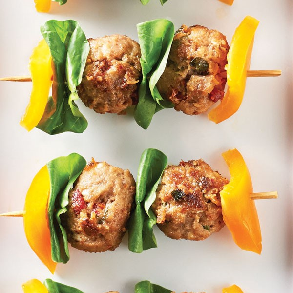 Yellow bell pepper, spinach, and meatballs on wooden skewers