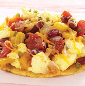 Corn tostada topped with scrambled eggs, melted cheese, kidney beans, and salsa