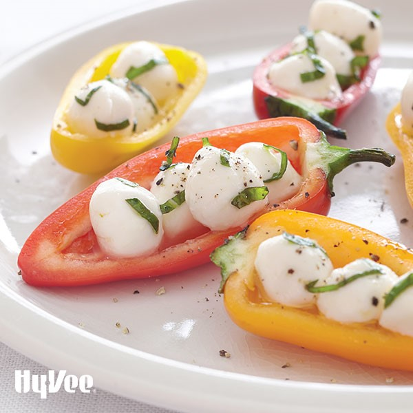 Halved mini bell peppers filled with fresh mozzarella pearls and garnished with chopped basil and black pepper