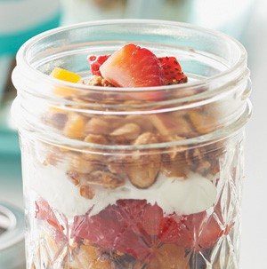 Mason jar layered with fresh fruit, granola, and yogurt