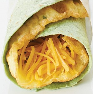 Spinach tortilla wrapped around omelet filled with shredded cheese
