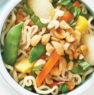 Noodles topped with peas, basil, red and yellow bell pepper strips and garnished with chopped peanuts