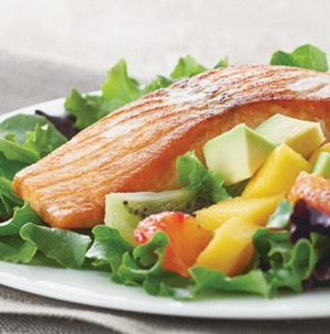 Salmon and avocado and mango salad served atop a bed of lettuce