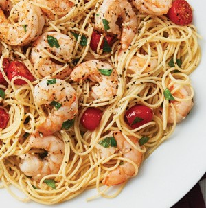 Pasta topped with shrimp, cherry tomatoes, parsley, and freshly cracked black pepper