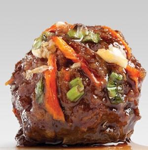 Teriyaki glazed meatball topped with fresh shredded carrots and sliced green onions